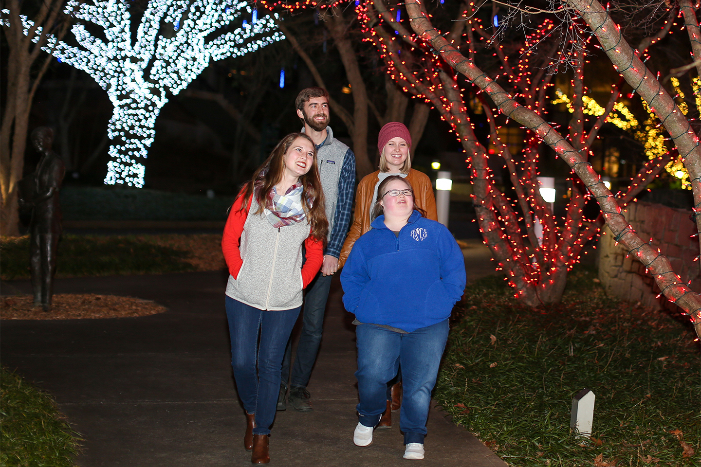 A family walks past trees lit with lights