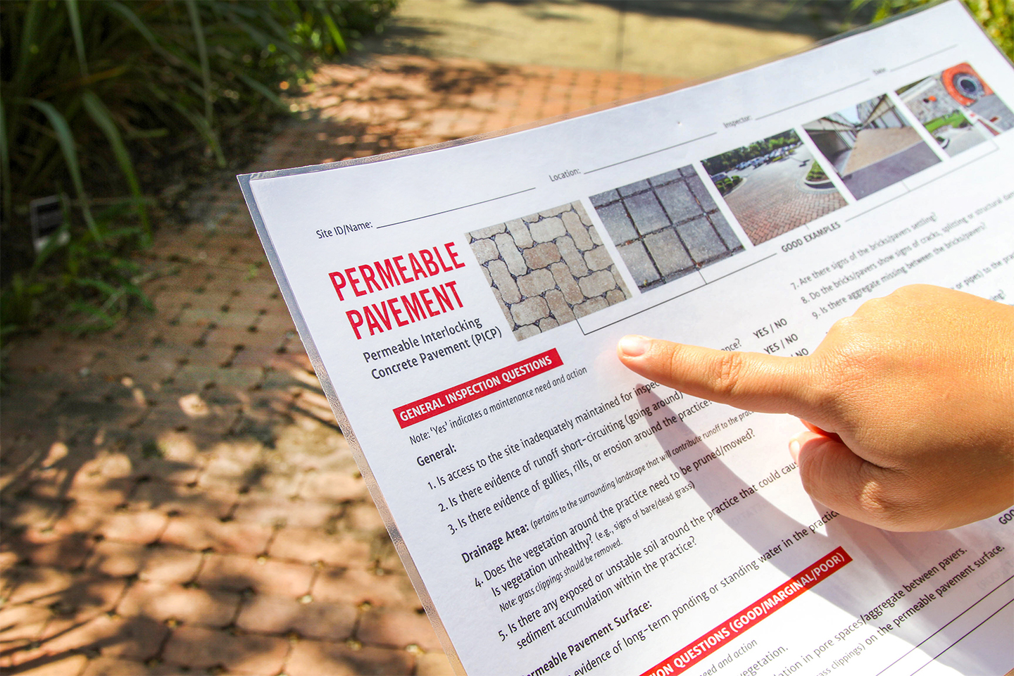 A finger points at a laminated document about permeable pavement options