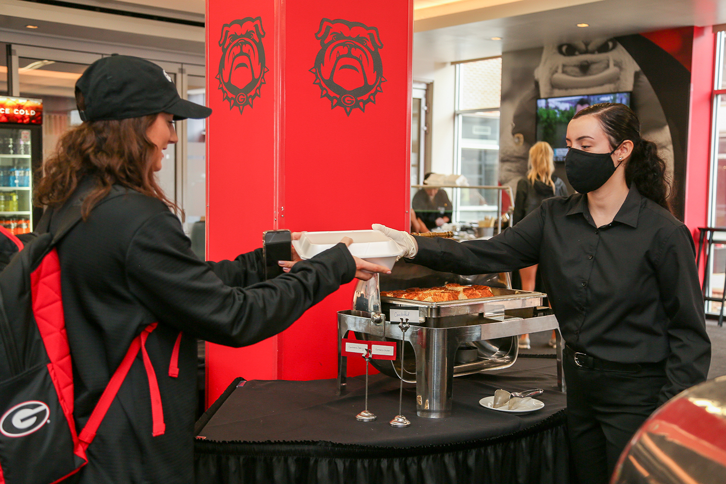 A UGA intern serves food to a student athlete at the Georgia Center.